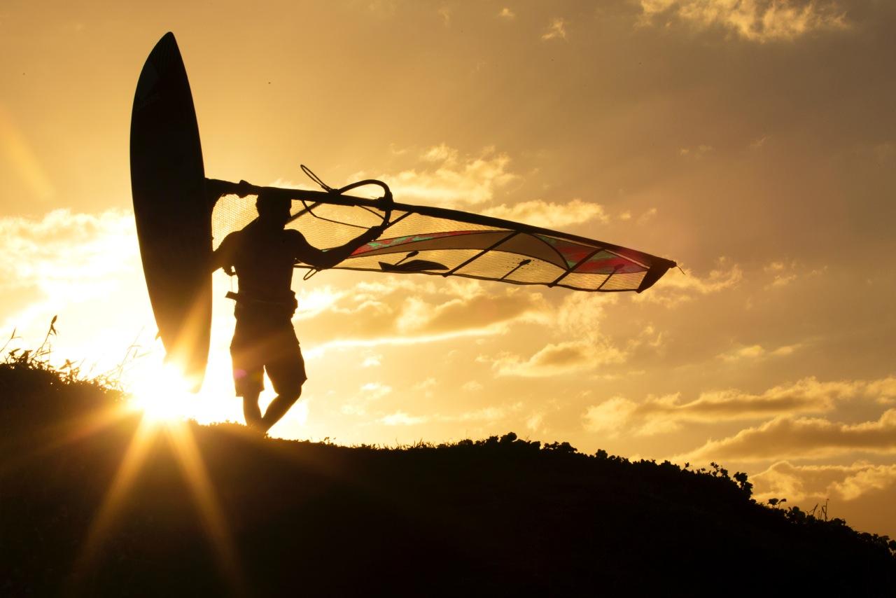zapad slnaka na pobrezi s windsurf doskou